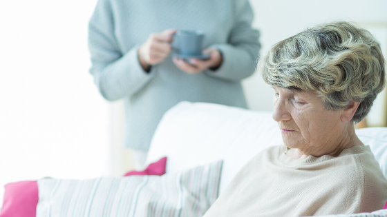 Older woman sits on couch looking upset while another woman stands holding a cup of coffee in the background