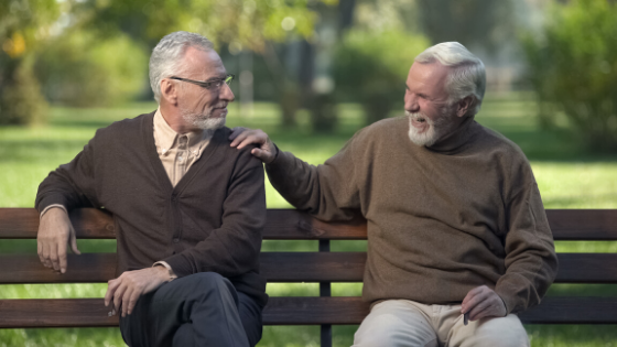 Two men in sweaters sit on a bench at the park talking and smiling