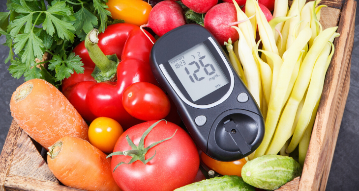 A blood glucose level of 126 is seen displayed on a meter surrounded by fresh vegetables