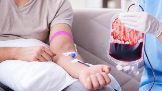 A person is seen getting a blood transfusion at home