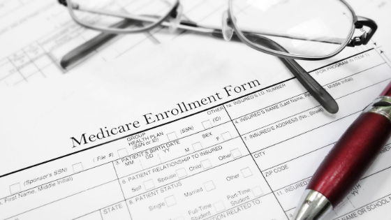 Medicare Enrollment forms with a pen and glasses