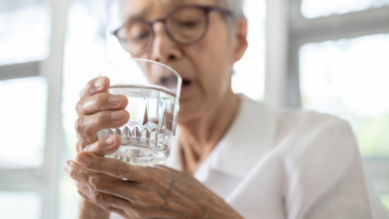 older woman holding a glass of water with both hands