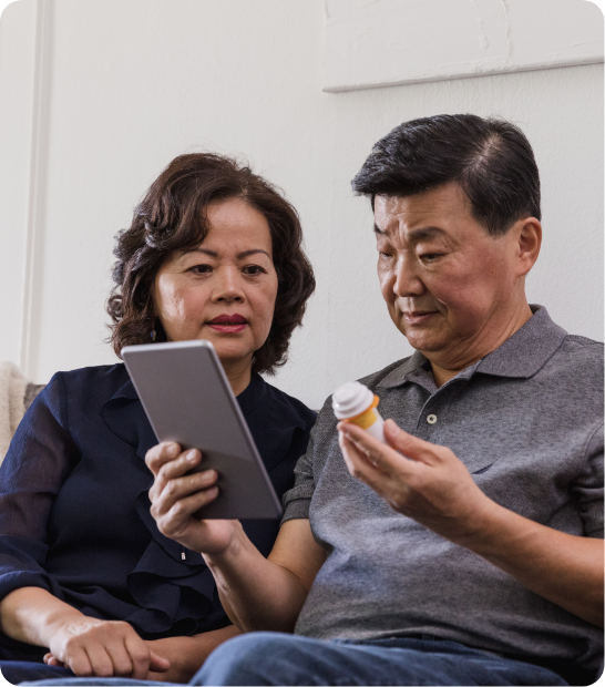 Senior couple reviewing medication instructions on tablet.