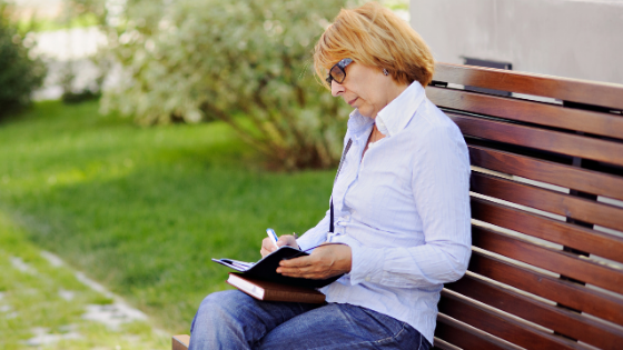 A woman sits on a park bench writing in a joural