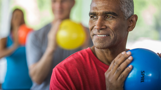 An older man is seen squeezing an exercise ball in a group class