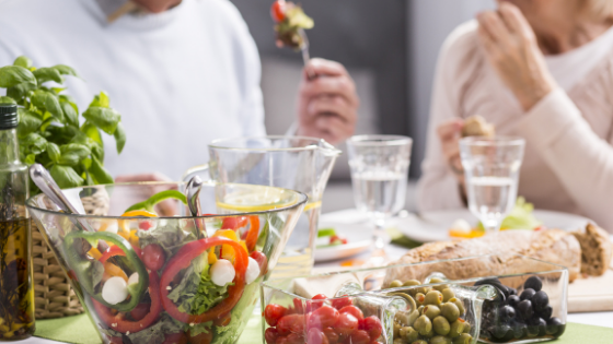 A close up of a full dinner table of healthy foods being shared by two people