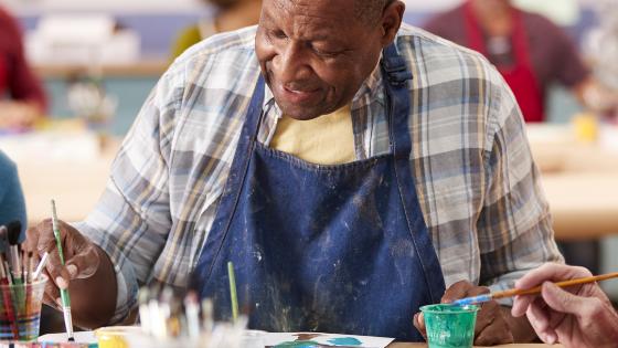 An older gentleman is seen painting in an art class