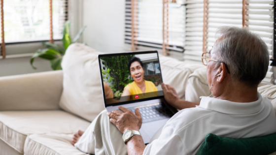 An older man is seen laying on the couch while video chatting a woman in yellow