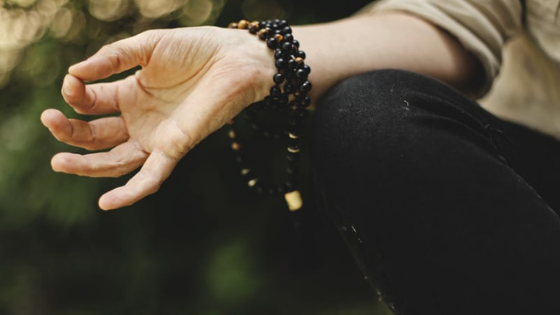 Close up of a woman's hand as she meditates, wearing beaded bracelets