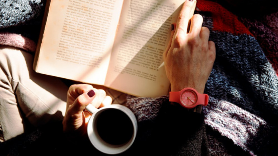 Aerial shot of a woman sitting cross-legged reading a book holding a cup of coffee