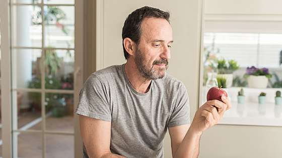 An oldr man is seen holding an apple and staring at it