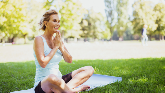 A senior woman is seen smiling as she meditates in a park