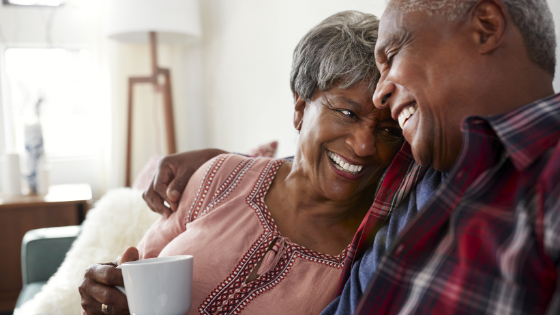 A senior couple are seen smiling close together in their living room