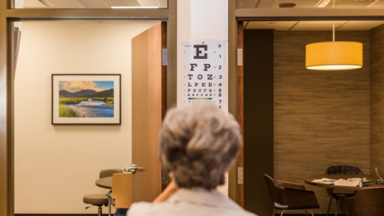 From behind, a older woman is seen taking an eye test