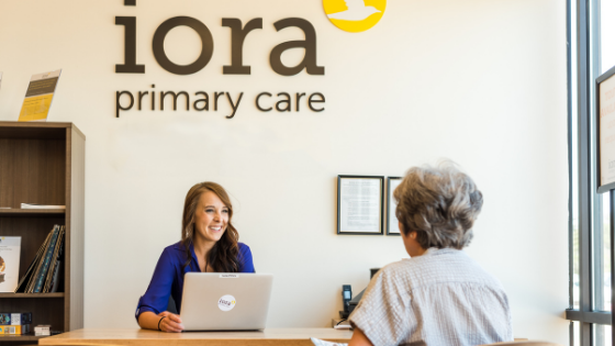 An older woman can be seen talking to an Iora Primary Care Operations Assistant