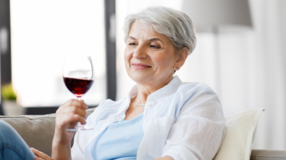 A senior woman sits on the couch holding a glass of red wine
