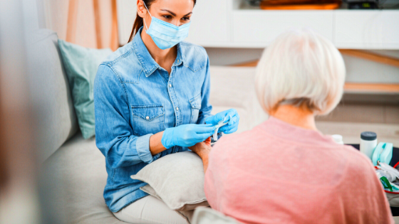 A doctor and patient are seen wearing masks as the doctor prepares to give a flu shot