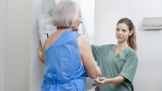 A senior woman can be seen getting a mammogram by their provider