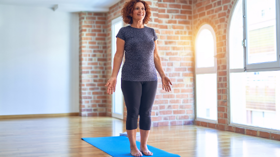 A senior woman is seen doing mountain pose on her yoga mat