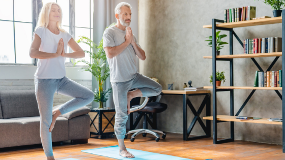 A senior couple is seen standing in tree pose on their yoga mats in the living room