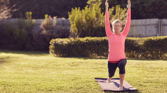 A senior woman is seen in Warrior I pose on her yoga mat in the backyard