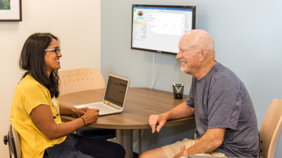 A senior man talks with his physician as they review his medical chart