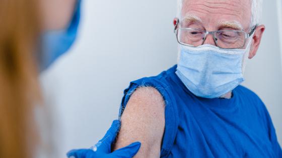A senior man is seen wearing a mask as he receives his flu shot