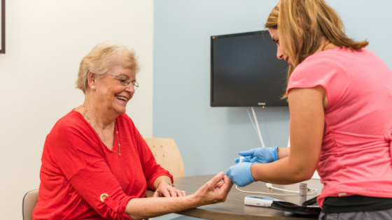 A senior woman with diabetes is seen having her blood sugar levels checked
