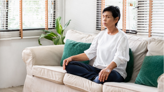 An older woman is seen sitting cross legged on her ouch, eyes closed