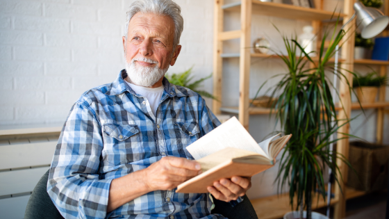 An older man in plaid stares off as he holds a book open