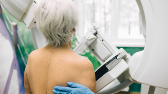 From behind, a woman with white hair is seen getting a mammogram