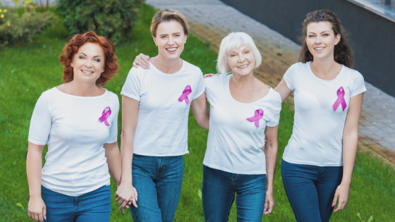 Three generations of women wearing pink breast cancer ribbons stand side by side outside