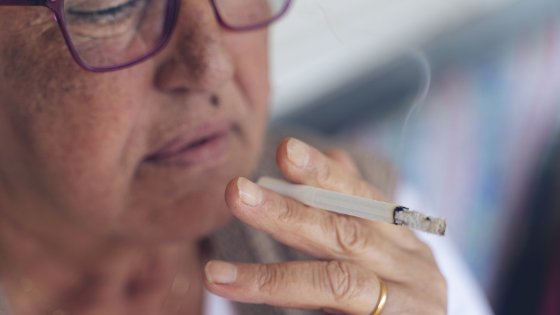 Close up of an older woman with glasses smoking a cigarette