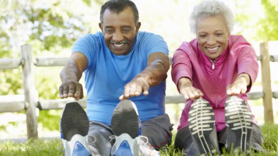 A senior couple stretches outdoors
