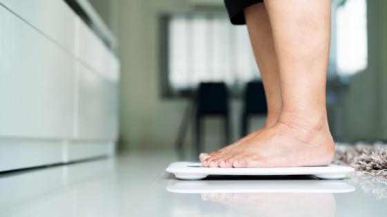 An older person's feet can bee seen standing on a scale