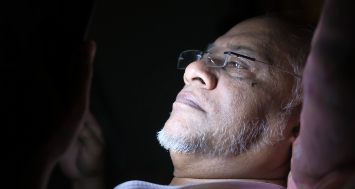A man's face is lit by a cell phone laying in bed