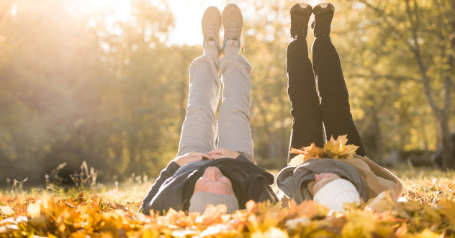 Two seniors lay in the leaves with their legs pointed at the sky