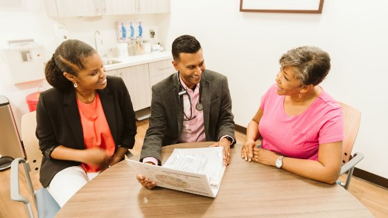 A female patient meets with her primary care physician and health coach to review her charts