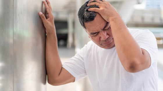An older man is seen gripping his head in pain leaning against a wall