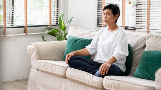 An Asian senior woman is seen sitting cross legged on a couch taking deep breaths