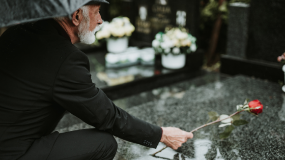 An older man is seen placing a rose on a grave
