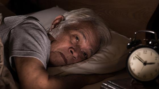 An Asian senior man lies awake in bed