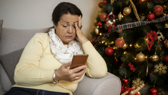 An older woman looks upset holding her phone next to a Christmas tree