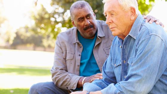 A Black senior man conforts his friend in a park