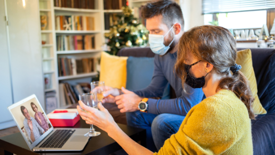 Couple wearing masks while they FaceTime with family for the holidays
