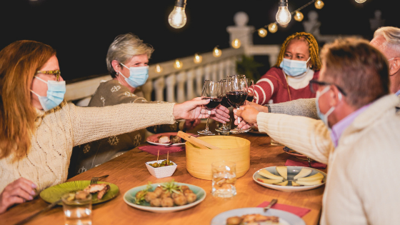 Guests are seen wearing masks and dining outdoors while they cheers