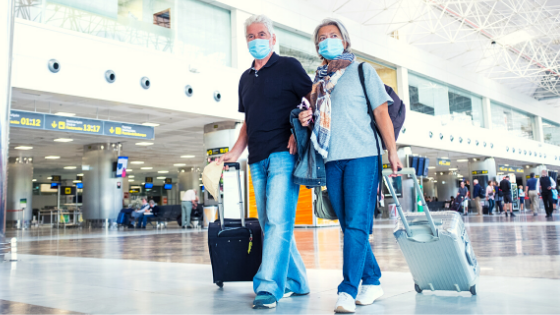 A senior couple is seen wearing masks as they walk through an airport with their luggage