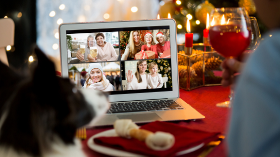 A man and his dog are seen having a virtual holiday dinner with family over Zoom