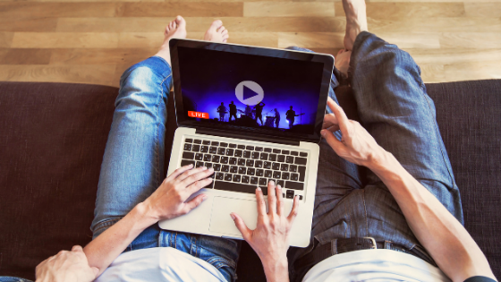 A couple are seen watching a live concert from their laptop