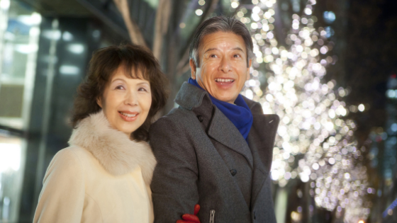 An Asian senior couple marvel at an outdoor holiday light display
